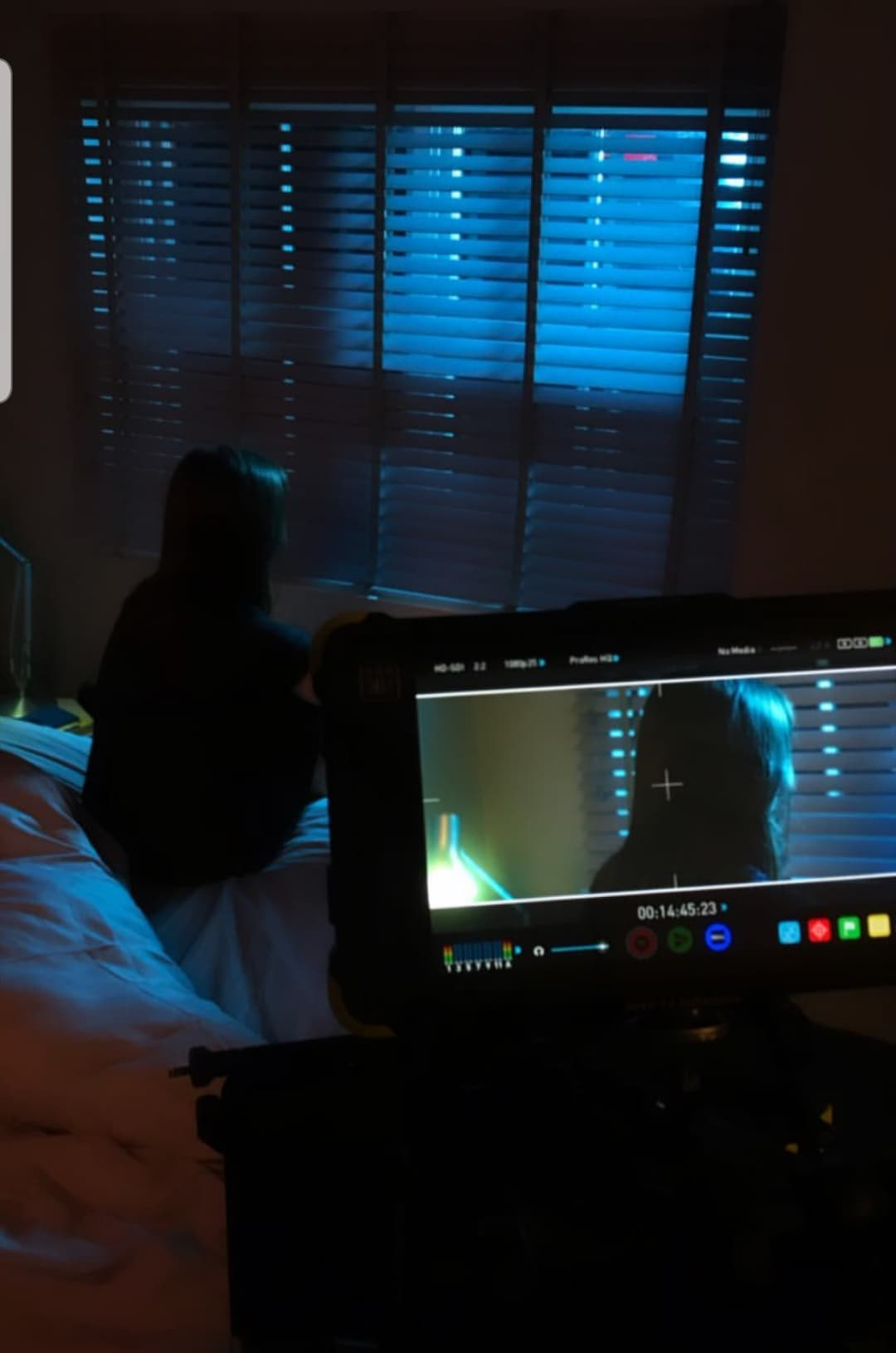 Viewed through a monitor on set, Katherine faces a moonlit window